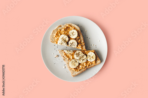 Photo Peanut butter chia seed banana toast for breakfast on a pink background, healthy
