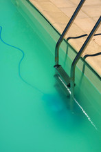 Swimming Pool Maintenance - An Automatic Robot Pool Cleaner Can Just Be Seen On The Bottom Of A Cloudy Swimming Pool Removing Debris And Algae.