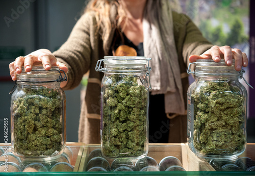 Photo  Glass jar full of Cannabis Sativa for sale at a market stall.