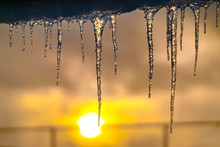 Translucent Icicles Hanging From A Roof At Sunset