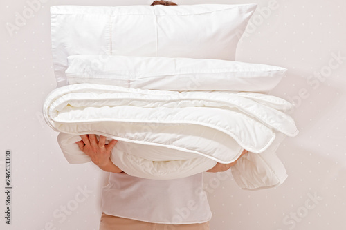 Fotografie, Obraz  Woman holding a pile of bedding for sleeping. Household