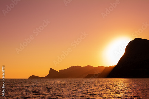 mountains in the sea at sunset