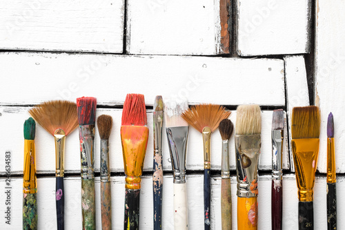 Fotografía  Artist's tools, dirty brushes in paint lie in a row on a white wooden background