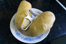 Two Potatoes And A Peeler On D...
