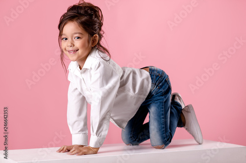 smiling little girl in white shirt with hairstyle looking to camera Canvas Print