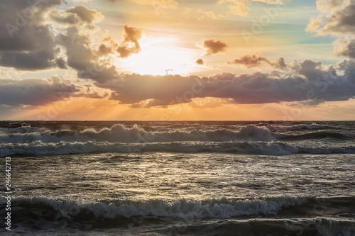 sunset in the cloudy sky over the stormy sea