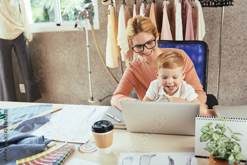 Fotografía  Cheerful female fashion designer working on laptop with son on her laps