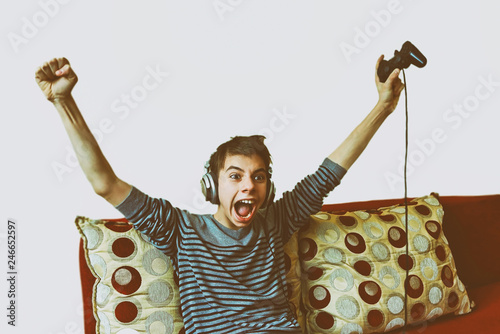 Photo teenage boy with headphones on his head emotionally screaming playing video game