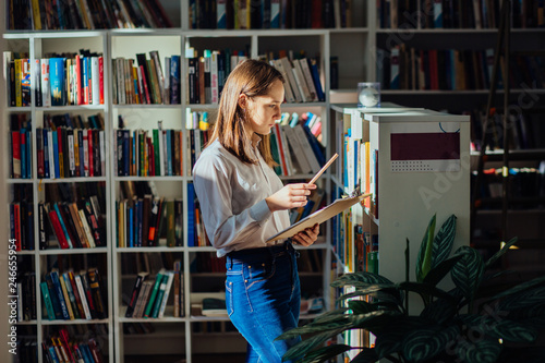 Student in library - smiling young female teenager search a book stand at bookshelf n college library Poster Mural XXL