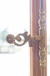 Iron forged door handle painted in bronze color. The decor of the room. Work with iron. Wooden door with a large glass. Flower pattern.