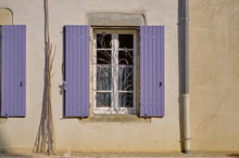 French Window With Mauve Shutters.  Texture Terracota Walls, And Wrought Iron Display In Window