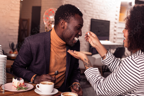 Fotografia  Delighted positive man trying a cake from his girlfriend