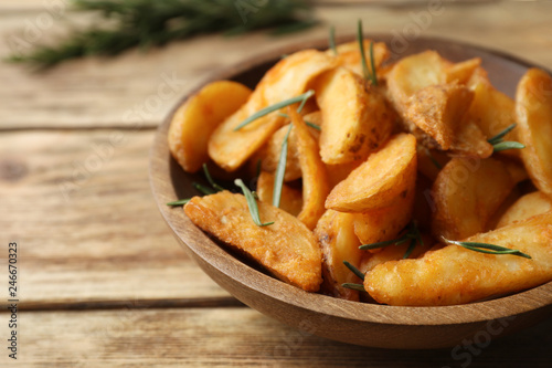 Fotobehang Aromatische Plate with baked potatoes and rosemary on wooden table, closeup