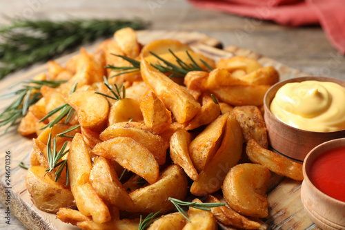 Fotobehang Aromatische Baked potatoes served with rosemary, ketchup and mayonnaise on wooden board