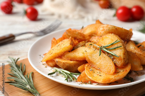 Fotobehang Aromatische Plate with tasty baked potatoes and rosemary on wooden board