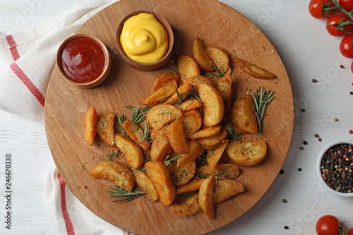 In de dag Aromatische Baked potatoes served with rosemary, ketchup and mustard on table, top view