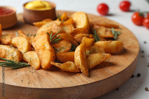 Fotobehang Aromatische Wooden board with baked potatoes and rosemary on table, closeup