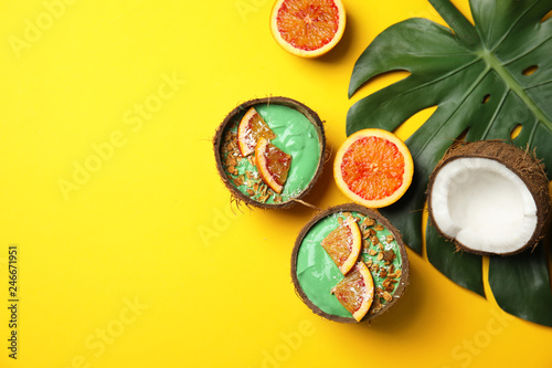 Coconut shells with yummy spirulina smoothie on color background, top view. Space for text