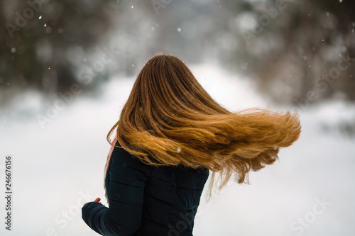 Girl's long hair. Fluttering beautiful сurls of young woman in winter outdoors.