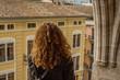 Mujer rubia mirando por el balcón