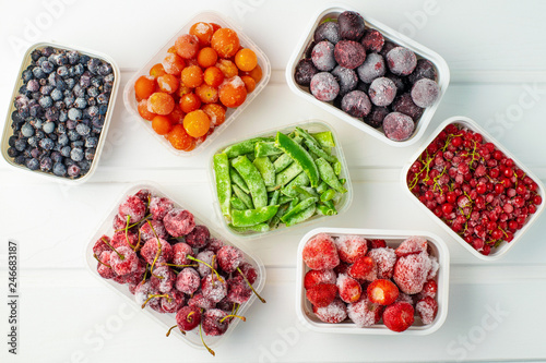 Obraz Frozen berries and vegetables in plastic boxes on white wooden background - fototapety do salonu