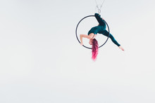 A Young Girl Performs The Acrobatic Elements In The Air Ring. Studio Shooting Performances On A White Background.