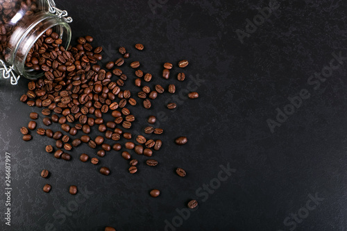 Fotomural Fragrant coffee beans are scattered from a jar on a rustic tabletop background