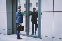 Serious Man In A Suit With A Briefcase Hurries To A Meeting In The Business Center. Businessman Opens Office Door. Business Life In The City.