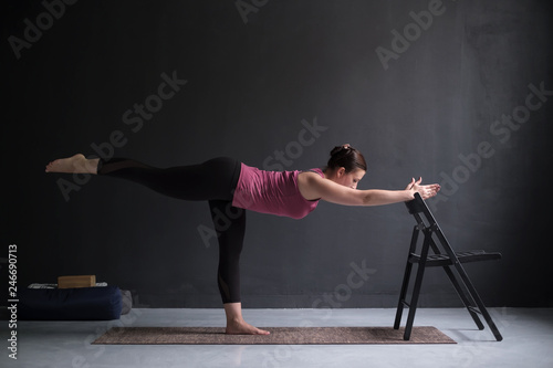 Woman show warrior asana using chair in studio background Wallpaper Mural