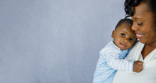Beautiful African Amercian Woman WHolding Her Baby Boy On A Gray Background