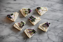 Diamond Shaped Cookies With White, Purple, And Green Frosting