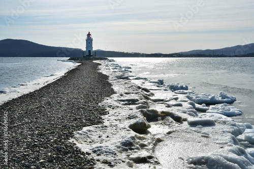 Russia. Vladivostok. The lighthouse of Egersheld(1876 year built) Tokarevskaya koshka in January in Amur bay. Photo in the background light