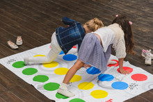Two Children Playing Twister On The Floor