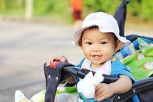 A Happy Baby Child Girl Sitting In A Stroller At The Garden. She Holding A White Flower In Her Hand.
