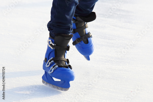 legs in blue skating on the ice rink