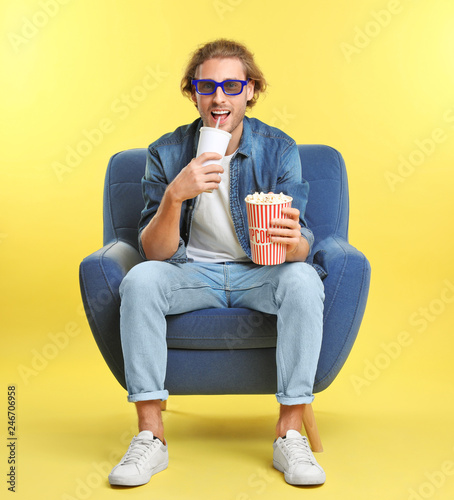 Man with 3D glasses, popcorn and beverage sitting in armchair during cinema show on color background