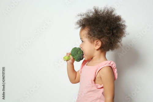 Cute African-American girl eating broccoli on white background. Space for text