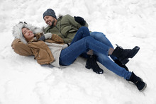 Happy Couple Lying On Snow Out...