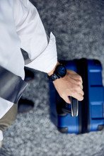 Man Wearing Dress Shirt And Blue Watch Holding A Blue Rolling Suitcase