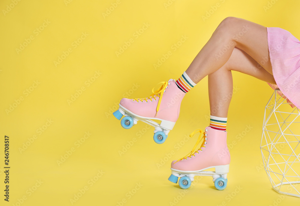 Young woman with retro roller skates on color background, closeup. Space for text