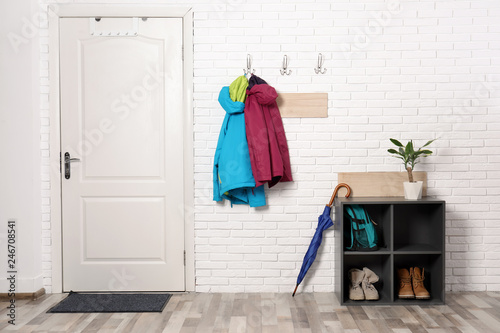 Fotografía  Stylish hallway interior with shoe rack and hanging clothes on brick wall