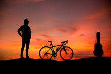 Silhouette Young Men With Guitar And Bicycles At Sunset