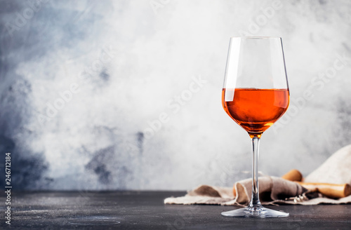 Foto op Canvas Alcohol Trendy food and drink, orange wine in glass, gray table background, space for text, selective focus