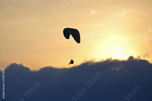 Paraglider flying on a wing in the sky against the setting sun