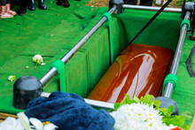 Burying A Coffin At Cemetery During A Funeral Ceremony