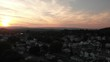 Aerial View of Hills and Houses in Small Town at Sunset PAN LEFT SLOW MOTION
