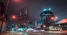 Timelapse At Crossing With Traffic Lights, Neon Lights, Fast Clouds Above, And Skyscrapers And Construction Sites In London, Night Time, 4k