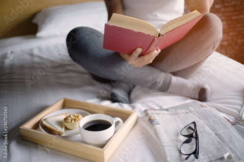 Happy woman reading a book and relaxing comfortably at home. Canvas Print