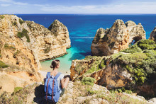 Young Woman Traveler Looking At The Sea In Lagos Town, Algarve Region, Portugal. Travel And Active Lifestyle Concept