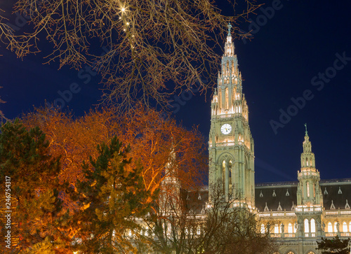 plakat Vienna, Austria, town hall building in the evening. The building is built in the neo-Gothic style with a symmetrical main facade. The main facade of the town hall has 5 towers.